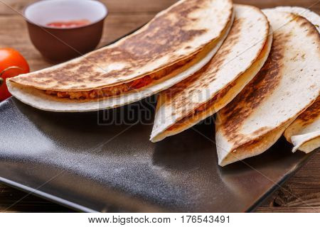 Photo of quesadilla with meat on wooden table