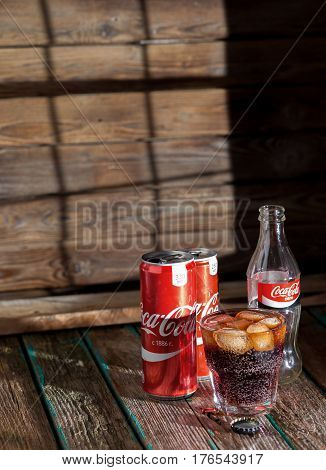 MINSK, BELARUS-MARCH 8, 2017: Can and glass of Coca-Cola with ice on wooden background. Coca-Cola is a carbonated soft drink sold in stores, restaurants, and vending machines throughout the world