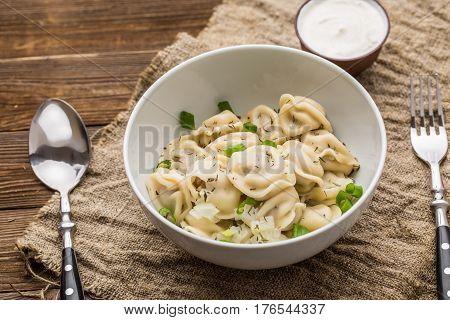 Meat dumplings - russian pelmeni, ravioli with meat on a white plate on a wooden background