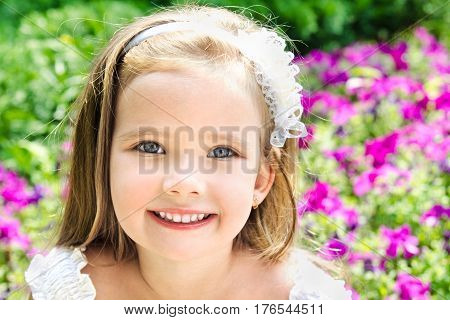 Portrait of adorable smiling little girl in summer day outdoors