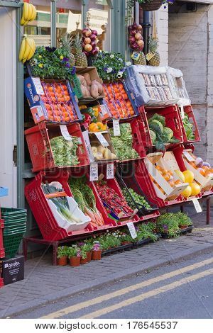 Llangollen Wales UK - March 15 2017: Traditional fresh fruit and vegetables pavement display outside a small independent Welsh green grocers shop. Pavement displays have long been used to display produce.
