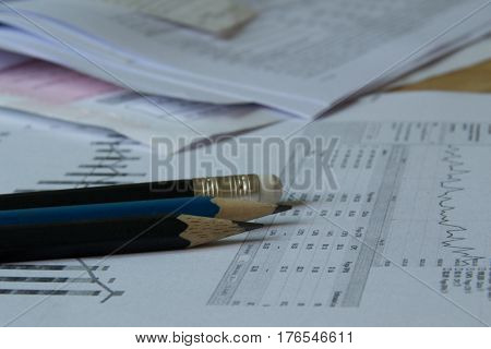 Accountant jobs on wood table include pencils, graph paper.