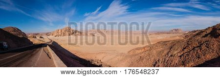 Wide panorama with road in desert, cloudy sky and rocks