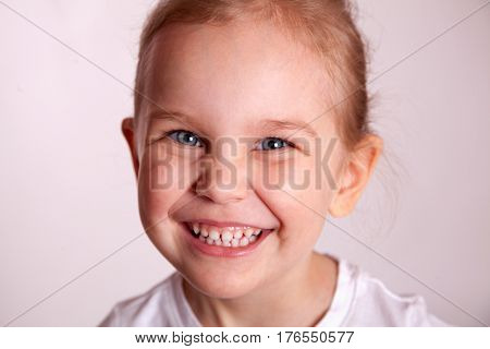 Closeup portrait of cute kid girl isolated on white background, adorable child having fun in studio, happiness concept