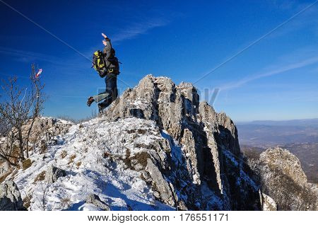 Happy mountaineer jump into the air on the top of the mountain
