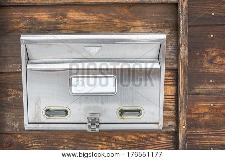 Aluminum mailbox hanging on the wooden wall