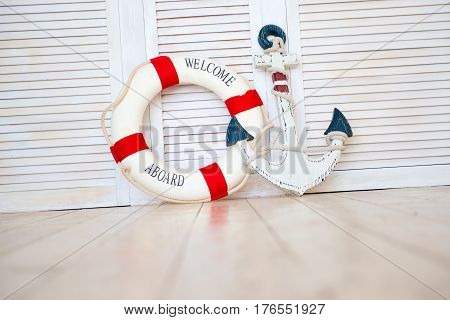Composition on the marine theme with anchor and lifeline on wooden background.