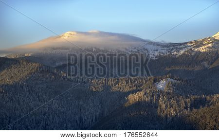 Winter mountains. Cloud has covered mountain top. Snowy forest in foreground. Blue clear sky in background.
