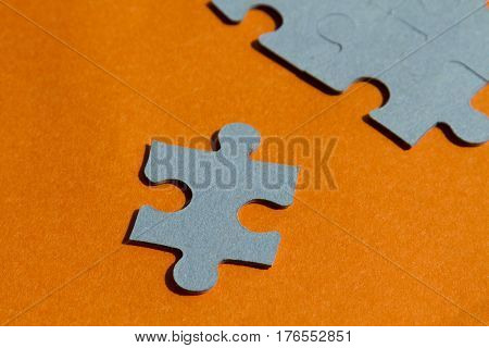 Jigsaw puzzle pieces on bright orange background horizontal view with copy space