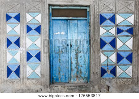 Rethymno Island Crete Greece - June 23 2016: Traditional Greek facade of house with blue wooden door and blue and white colored patterns on the gray wall