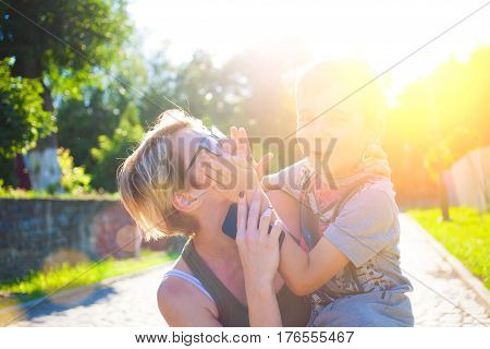 A woman holds a son in her arms and hugs him mom messing around with a child.