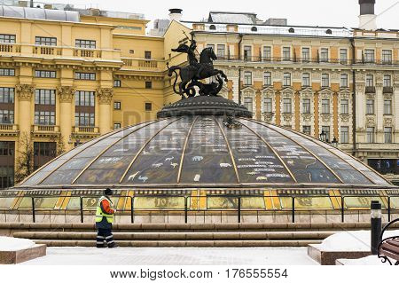 Moscow, Russia - February 1, 2017: Janitor cleans snow on Manezhnaya Square at the fountain World Clock in Moscow