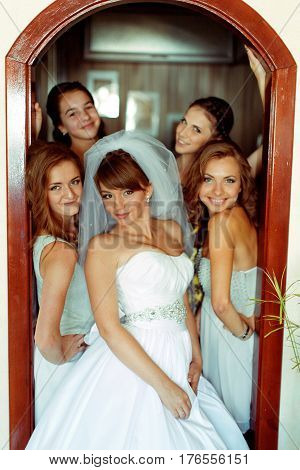 Bride Poses In Doors Surrounded By Pretty Bridesmaids