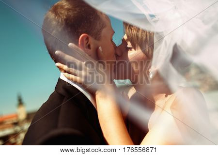 A Closeup Of A Bride Kissing A Groom In The Front Of Lemberg's Roofs