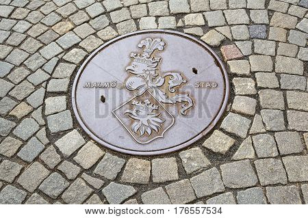 Street manhole cover on cobbled road in Malmo Sweden.