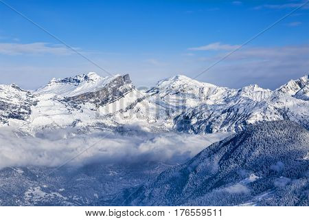 Beautiful rocky mountain peaks covered by snow above the clouds in Alps.