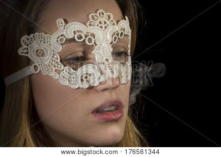 Young girl with lace mask and smoking