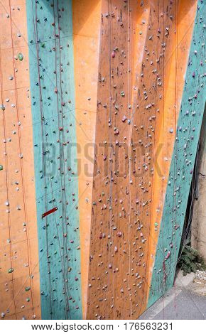 Wall of outdoor climbing Gym in green and orange colors with many holds and ropes