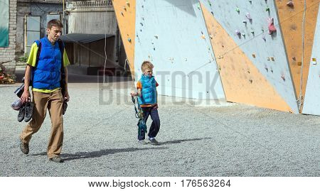 Family of father and son going to climbing wall carrying gear. Family Climbing Competitions Mother, Father and Me , Dnipro, Ukraine, September 18, 2016