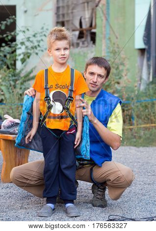 Family of father and son wearing gear preparing for climb the wall. Family Climbing Competitions Mother, Father and Me , Dnipro, Ukraine, September 18, 2016