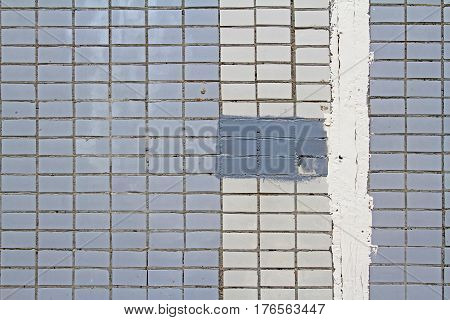 Mosaic tiles on the facade of a house. Architectural background made of blue and white mosaic wall with painted splotch and plastered slit