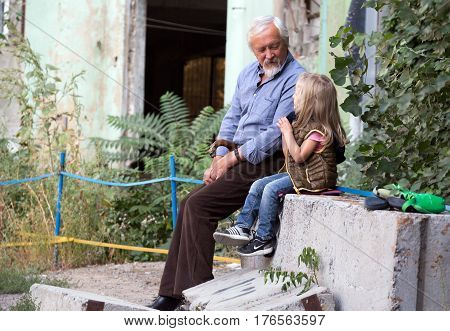 Mature Grandfather and little baby Granddaughter sitting and talking while watching the climbing competitions. Family Climbing Competitions Mother, Father and Me , Dnipro, Ukraine, September 18, 2016
