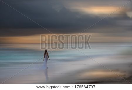 Beautiful white dressed woman walks at the beach. Blurred background.