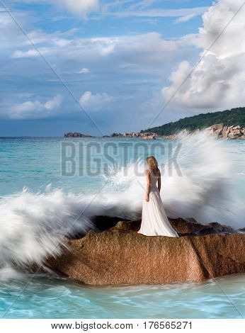 Beautiful woman stands on rock, splashing sea waves, white dress