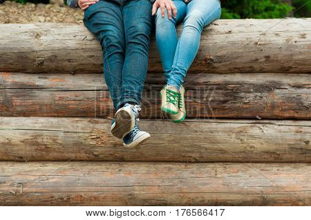 Male and female legs in keds and jeans. Stylish couple feet in love their legs