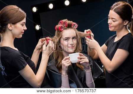 Hairstylists Curling Hair To Woman