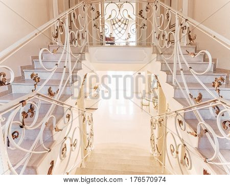 Staircase with marble steps and with ornamental iron handrail. Luxurious interior with gilded decorative nuances.