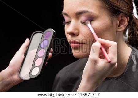 Hand of make-up artist applying eyeshadow on eyelid of model poster