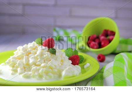 granular  cottage cheese  with  cream and fresh raspberries