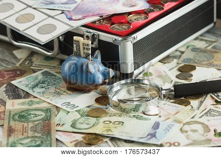 Different collector's coins and banknotes in the box with a magnifying glass and piggy bank soft focus background