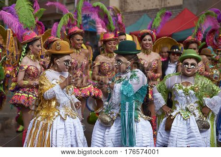 ORURO, BOLIVIA - FEBRUARY 25, 2017: Female Morenada dancers in colourful costumes parading through the mining city of Oruro on the Altiplano of Bolivia during the annual Oruro Carnival.