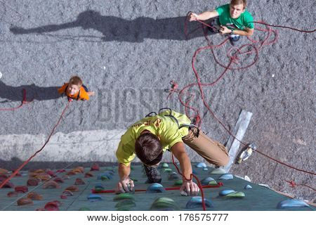 Father and son perform speed climbing relay race on vertical wall, belaying referee holding rope on ground. Family Climbing Competitions Mother, Father and Me , Dnipro, Ukraine, September 18, 2016