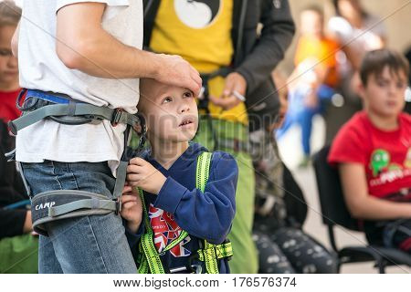 Father and little son in climbing harnesses watching the race of rock climbers. Family Climbing Competitions Mother, Father and Me , Dnipro, Ukraine, September 18, 2016
