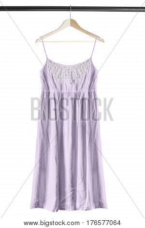 Purple linen sundress on wooden clothes rack isolated over white