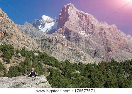 An attractive young woman doing a yoga pose for balance and stretching staying on top of rock in the mountains blue sky and sun