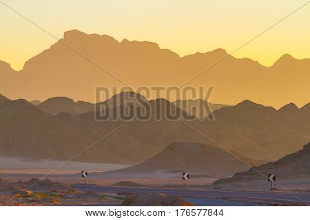 Dawn. The sun rises from behind the mountains in the Sinai desert