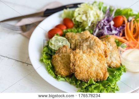 Crispy fried fish fillet with vegetables on wooden table