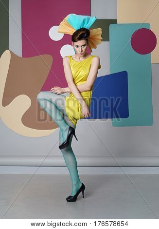 Active woman in yellow running, looking up from ground. Fashion-story, Danish design. Color composition. Eccentric outfit. Short dress, high heels. Cyan tights. Simple shapes - circles, rectangles.