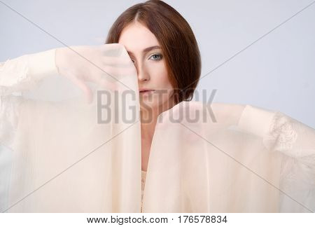 A stylish woman with a transparent shawl near the eyes. One eye is covered with a shawl. Scarf beige, emotional movement. Fashion, romance, actress, theater. Light, warm colors.