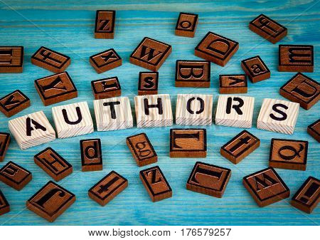 authors word written on wood block. Wooden alphabet on a blue background.