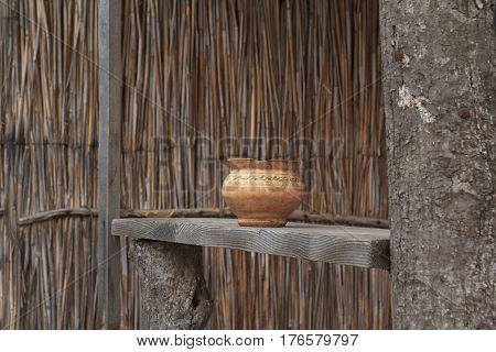 Antique orange handmaded clay pot with an ornament stands on a wooden sill with bulrush wall at background