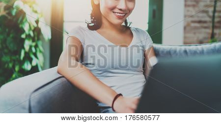 Portrait of attractive young Asian woman sitting at sofa and working modern laptop at home, wearing white tshirt.Horizontal, blurred backgroung, flare effect.Wide, crop