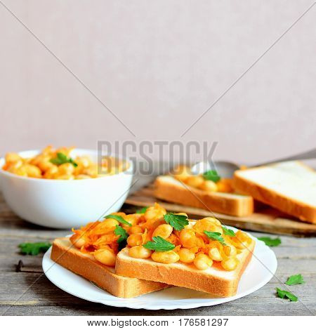 Vegetarian open sandwiches on a plate. Stewed white beans with vegetables and parsley on white bread slices. Healthiest food