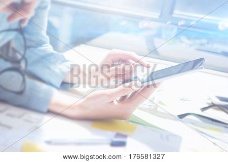 Closeup of female hands holding modern smartphone and touching screen.Concept business people using mobile gadgets.Icon and diagramm on display.Visual effect, color filter, blurred.Horizontal