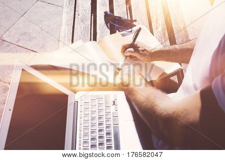 Closeup view of man sitting on bench and making notes on text book.Studying at the University, preparation for exams. Books, modern design laptop and sunglasses near him.Horizontal, flares effect