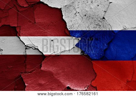 Flags Of Latvia And Russia Painted On Cracked Wall